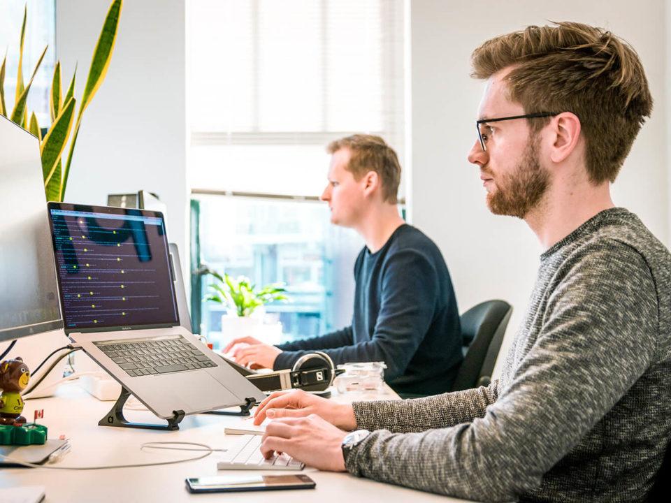 Zwei Personen arbeiten am Schreibtisch vor zwei Monitoren.